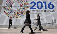 Pedestrians pass by a banner announcing the 2016 spring meetings of the IMF and World Bank on Wednesday in Washington DC. (Photograph Credit: Mandel Ngan/AFP/Getty Images) Click to Enlarge.