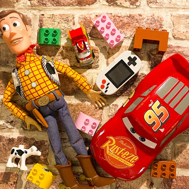 Selection of toys laid out including McQueen, Duplo and Woody