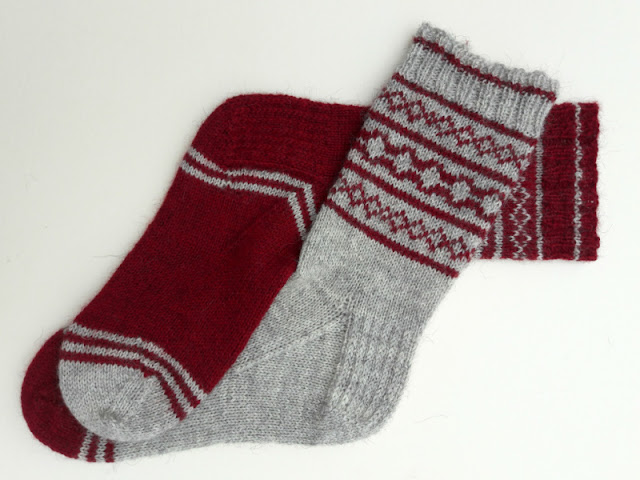 A predominantly red and grey colourwork sock laid next to a predominantly grey and red colourwork sock