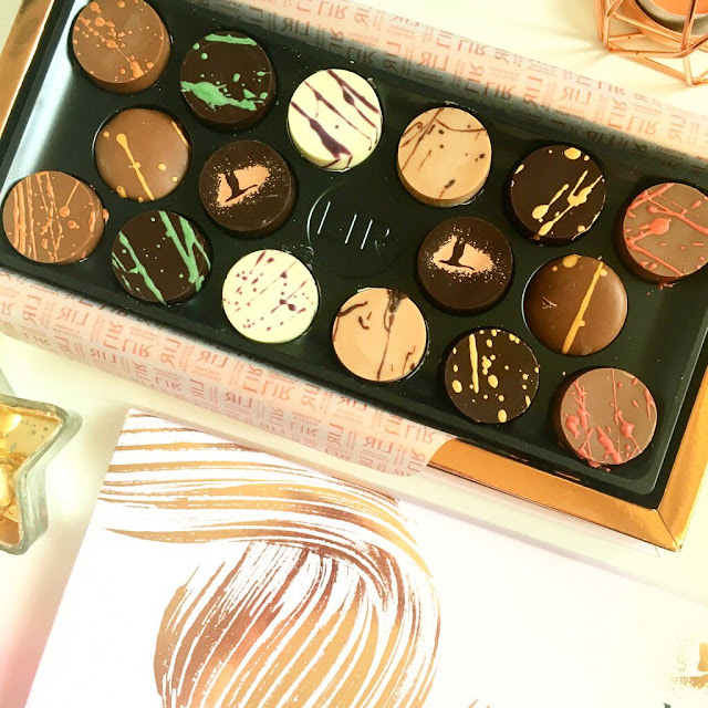 flatlay - Lir chocolates open, lid of box slightly in the photo at the bottom, star ornament in left space