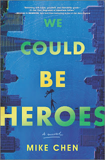 "Two city skylines, one on each side of the book. ""We Could Be Heroes"" is in large text across the book, and two small figures hang off of the letter ""B"" in ""Be"", one holding on to the other as they dangle in the air."