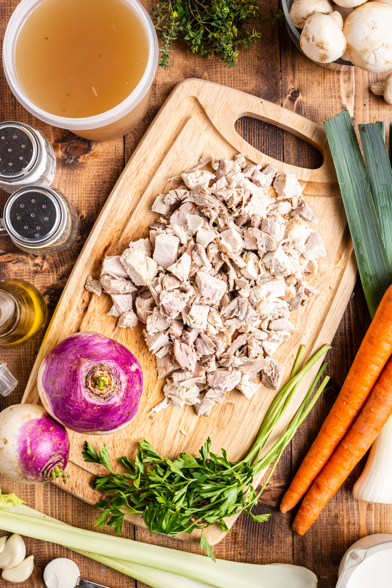 Overhead view of the ingredients for Creamy Low Carb Turkey Stew on a wooden cutting board.