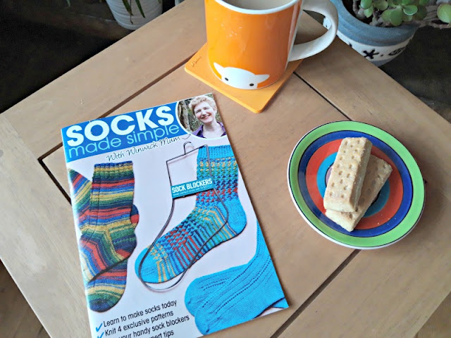 A photo of a small oak occasional table.  On the table to the left and in the foreground is a booklet of sock patterns called Socks Made Simple.  To the right is a small saucer decorated with circles of green, blue, red and turquoise with two shortbread fingers sitting on it.  At the top of the picture is an orange Herdy mug of tea