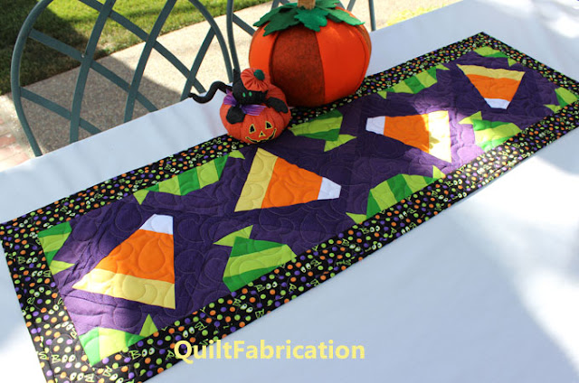 Halloween Candy table runner on a table with pumpkins by QuiltFabrication