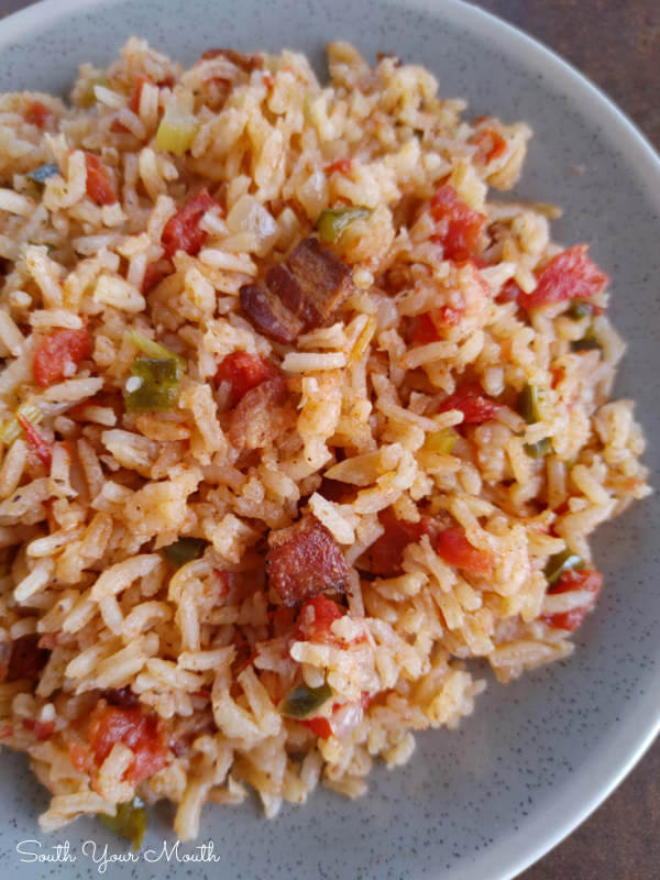Charleston Red Rice: A Lowcountry recipe popular from Charleston to Savannah, made from rice cooked with bacon and a tomato broth seasoned with peppers and onions perfected by the Gullah and Geechee. #redrice #charleston #gullah #southern #lowcountry
