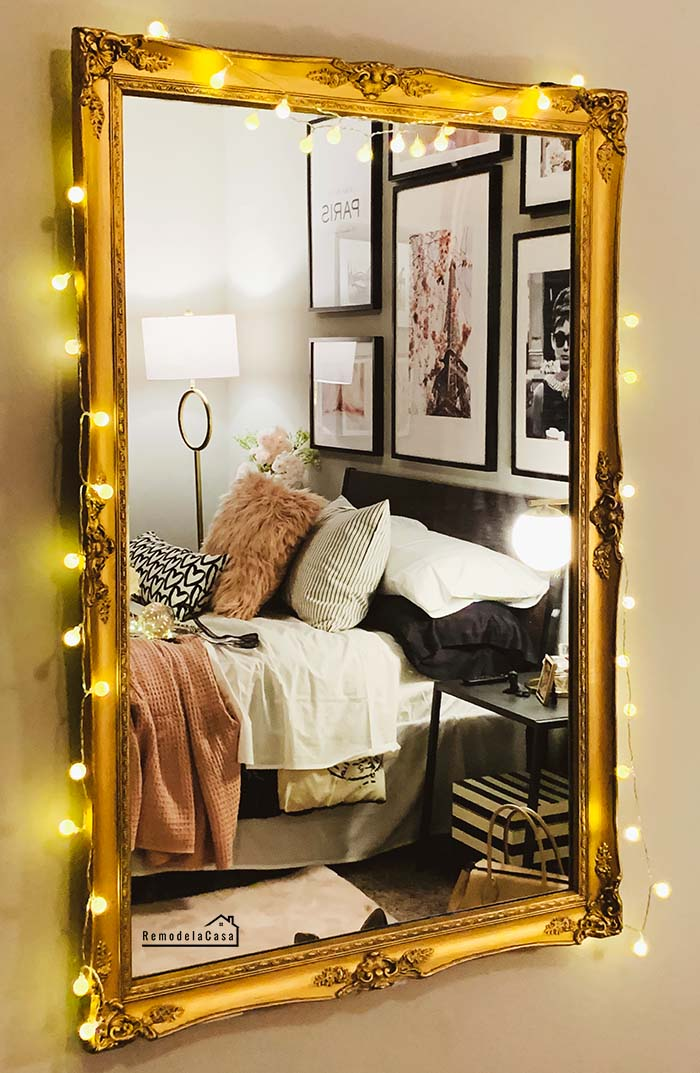 Paris bedroom with a gold mirror with string lights