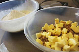 two mixing bowls; cubes of butter and brown sugar in one, and some flour in the other
