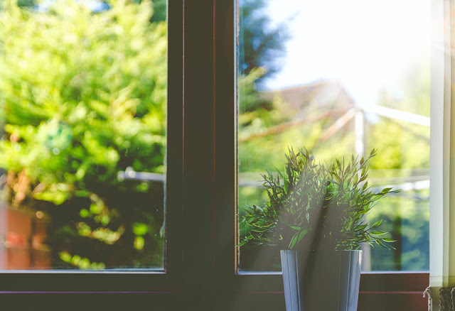 Close up of a window filled with sunlight with a plant pot placed on the window sill