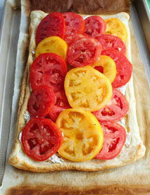layers of fresh yellow and red tomatoes on top of ricotta and puff pastry ready to bake