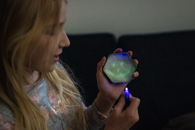 A girl in a dark room holding glow in the dark putty with a face glowing on it and holding a uv light
