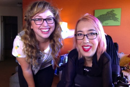Two young women smiling and facing the camera. Left has long, wavy blonde hair, wears glasses, and is somewhat crouched down. Right has medium blonde hair with pink highlights, glasses, and is sitting in a power wheelchair