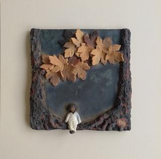 Cuadro de cerámica de mujer sentada sobre la raíz de un árbol