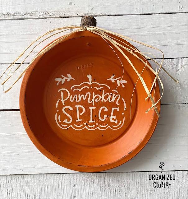 Photo of a pie tin repurposed as a wall decor pumpkin.