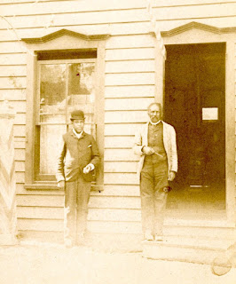 Two African American men standing in front of a building.