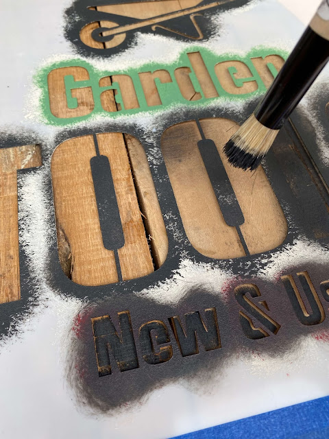 Photo of stenciling a wood sign