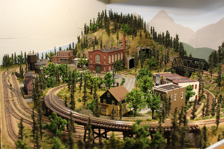 A completed 4 x 8 HO scale model railroad layout set in mountain forest scenery
