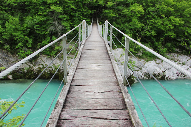 Crossing a suspension bridge over the Soca River - Slovenia