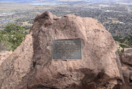 """With  distant scenery in the bacckround, a boulder with a metal plaque that reads """"Mount Sanitas: The trail along the east ridge of Mount Sanitas was constructed by volunteers for Outdoor Colorado in coordination with the City of Boulder Open Space Dept. On May 19th and 20th 1990."""