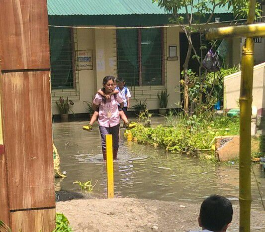 Grade school teacher carries her students in her back, to help them cross the flooded streets!