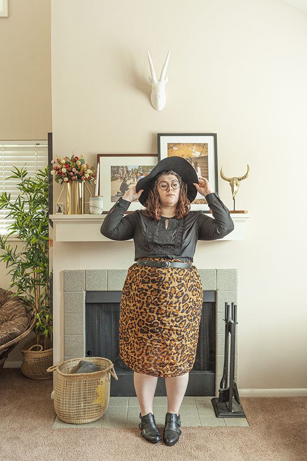 Black floppy hat, black peasant blouse, a leopard scarf tied and belted like a skirt, and black booties.