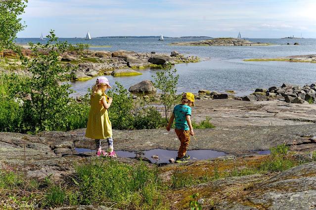 Lapset leikkivät rantakalliolla