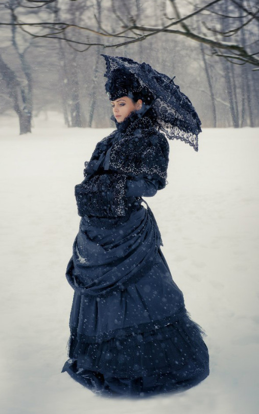 Woman dressed in Gothic Victorian clothing (black parasol, skirt, bodice, shawl, hat, and muff) in the winter snow. women's victorian cold weather clothing (winterwear)