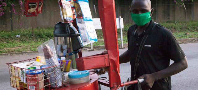Un vendedor informal de Costa de Marfil utiliza mascarilla para protegerse del coronavirus.ILO/Jennifer A. Patterson
