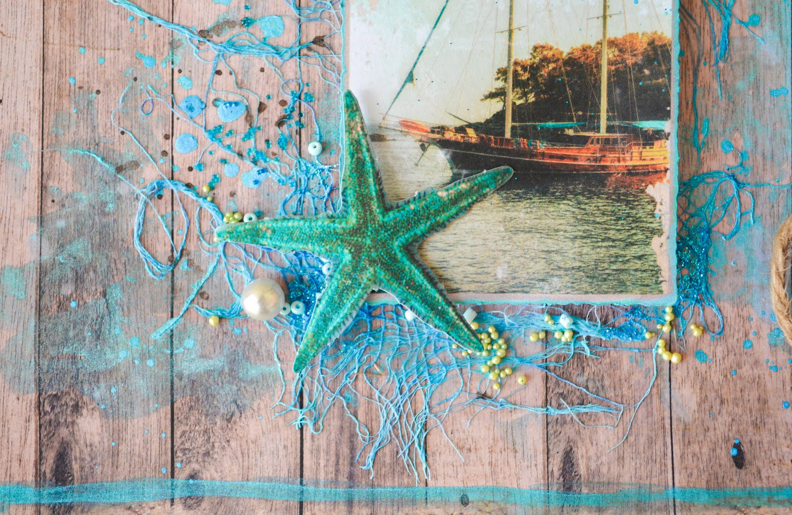 Nautical boat and seashells scrapbook layout page in turquoise blue on wood grain background with mixed media elements, cheesecloth, prills microbeads, jute rope twine, seed beads, and pearls
