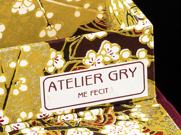 Kleines Schild mit der Aufschrift 'ATELIER GRY me fecit' auf dem Etui 'Goldener Fluss'
