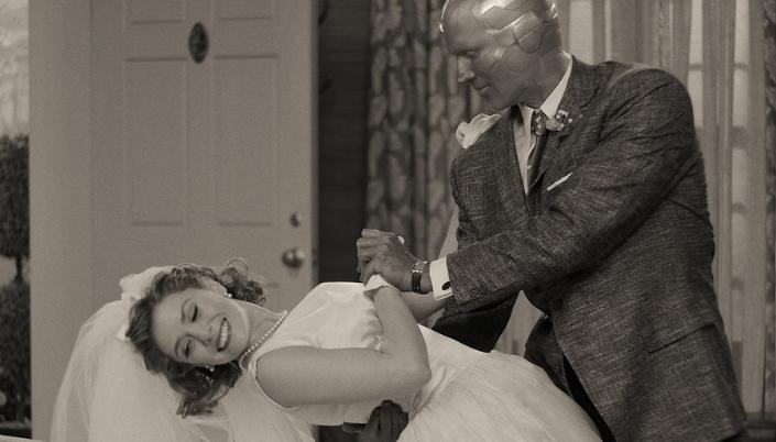 Imagem: Wanda em um vestido e casamento dançando com Visão que está de terno preto, ainda em forma de robô, numa casa de subúrbio que lembra os cenários de sticoms dos anos 50, a porta da frente ainda aberta, a foto em preto e branco.