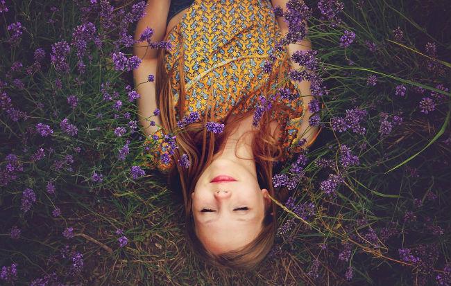Ragazza addormentata tra fiori di lavanda