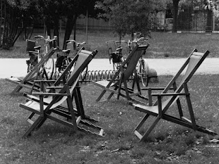 Black and white photograph of four wooden deck chairs on a lawn. There are bicycles, a path and shrubbery in the background giving the impression of a public park.