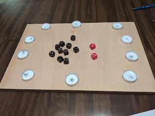 Ten used tea light candles in a circle on a wooden board, with several black dice and two red dice in the centre of the circle.