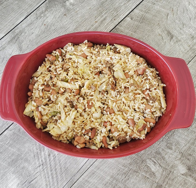 this is a red casserole dish with beans, rice and cabbage along with ground beef