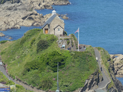Stone chapel on hilltop over rocky harbour