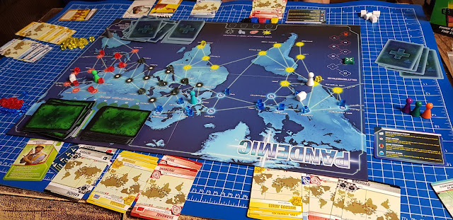 Pandemic gameplay large table and board layout pieces pawns cards