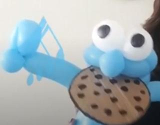 Ballonfigur vom Krümelmonster mit Keks im Maul.