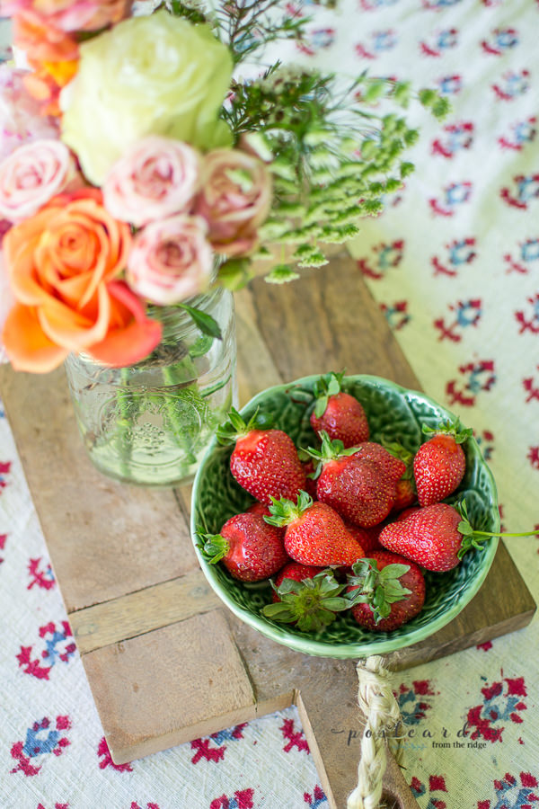 fresh strawberries in a green bowl on a wooden cutting board