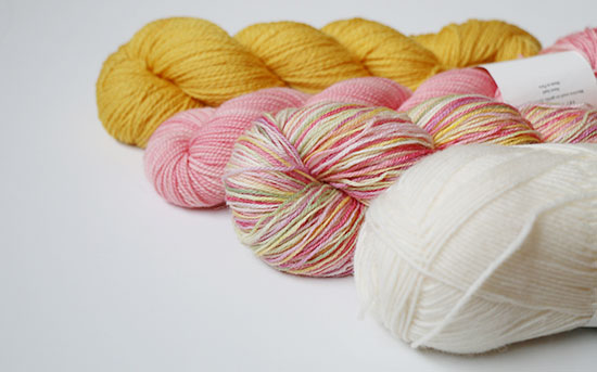 Four skeins of wool sock yarn on a white background: yellow, pink, multi-colored pastel, and ivory.