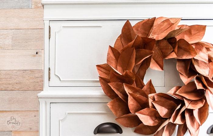 paper bag magnolia wreath hanging on dresser front