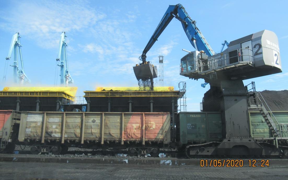 Vilciena vagons ar oglēm stāv pie izkraušanas celtņa