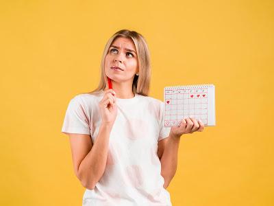Mujer con calendario de periodo menstrual