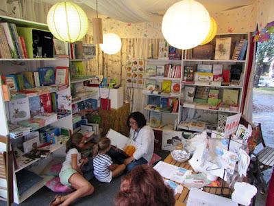 Senhora lendo um livro para crianças num stand de livros
