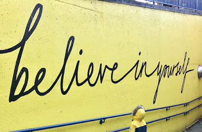 """""""Believe in Yourself"""" mural-black cursive on yellow background"""