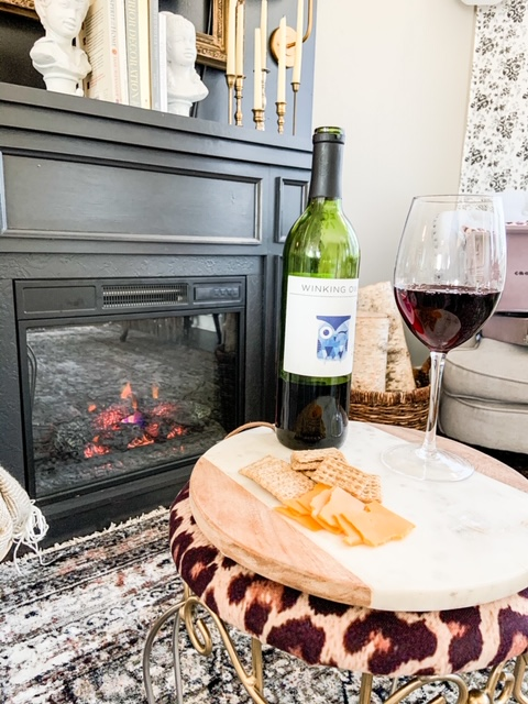wine and cheese by fireplace