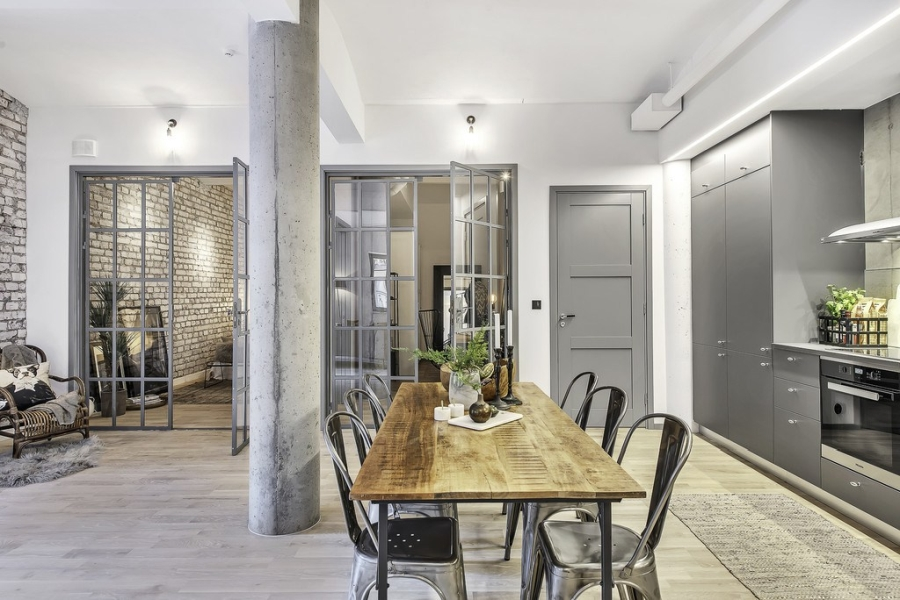 Apartament o przemysłowym charakterze, wystrój wnętrz, wnętrza, urządzanie mieszkania, dom, home decor, dekoracje, aranżacje, styl industrialny, industrial style, salon, kuchnia, otwarta przestrzeń, szare wnętrza, grey, living room, kitchen, ceglana ściana, ściana z cegły, brick wall