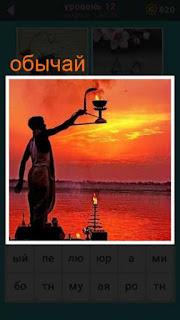 мужчина на закате совершает свой обычай с вытянутой рукой в сторону и держа лампу с огнем