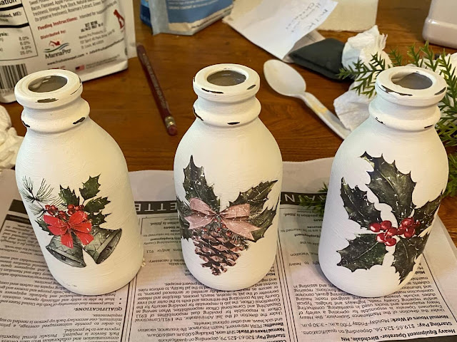 Photo of 3 chalk painted bottles with Christmas decor transfer designs.