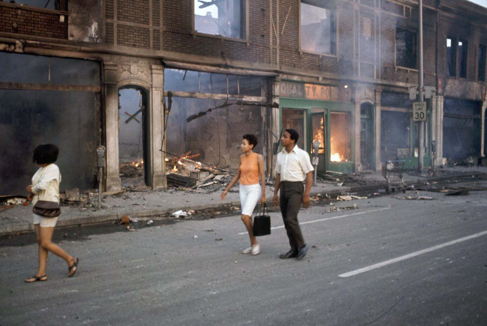 Detroit residents stroll the burning streets.