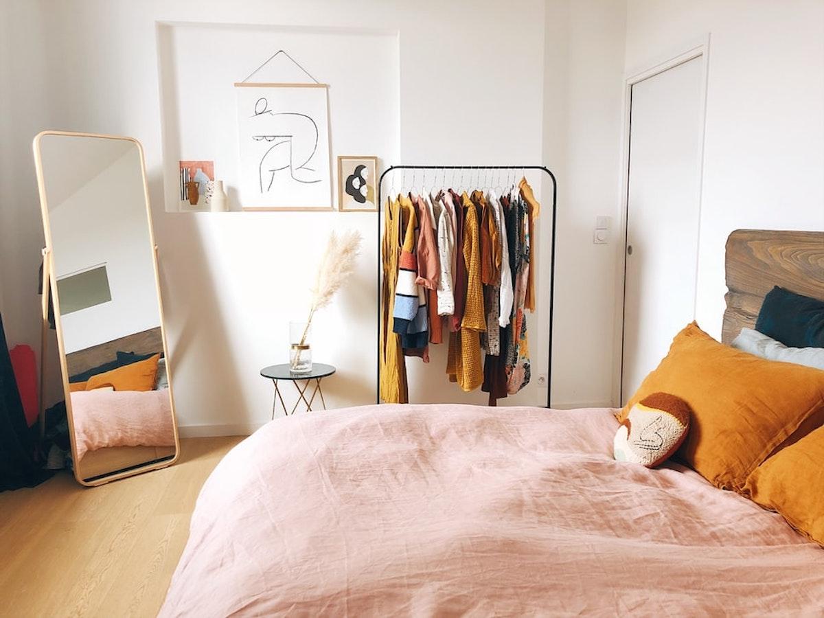 Dormitorio con espejo de pie y burro de ropa